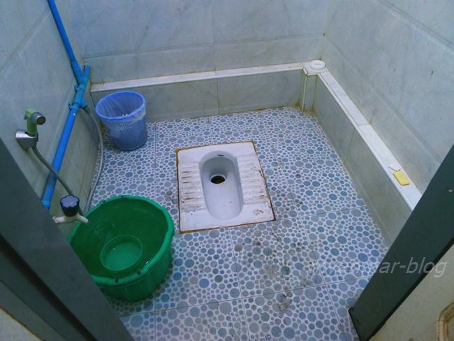 一般的なミャンマーのトイレ。手前のドアの方を向いてしゃがんで、バケツ(緑色)に汲まれた水を汲んで大切なところにかけて、洗います。